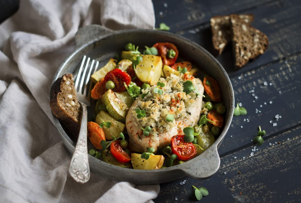 chicken breast baked with vegetables in a vintage pan on a dark wooden background