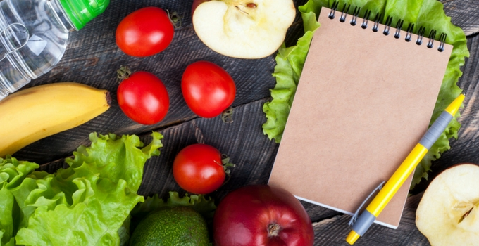 Meal Planning Saves Time and Money: Pen, notebook, tomatoes, lettuce, avocado, apple and a banana