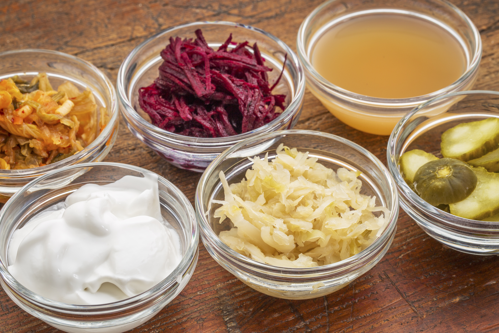 a sampler of fermented food great for gut health - glass bowls against wood: kimchi, red beets, apple cider vinegar, coconut milk yogurt, cucumber pickles, sauerkraut